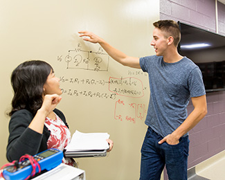 student and teacher doing math at a white board
