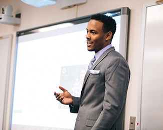 student in a suit in front of a powerpoint