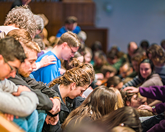 students praying for other students during convocation