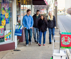 students walk through the downtown business district