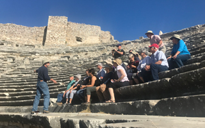 People sitting an greek ruins listening to a tour guide