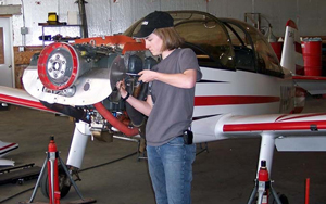 Student fixing an airplane engine