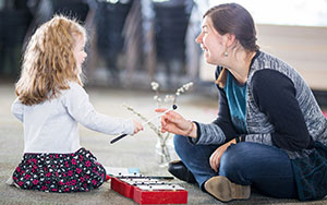 Child and teacher playing a zylaphone