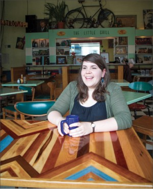 Alice Wheeler, who studied social work at EMU 2008-10, works part-time at The Little Grill while pursuing her dream of being a certified midwife. Here she sits at a table created out of reclaimed wood by Kurt Rosenberger, a 2006 art major who operates Grey Fox Design Works.