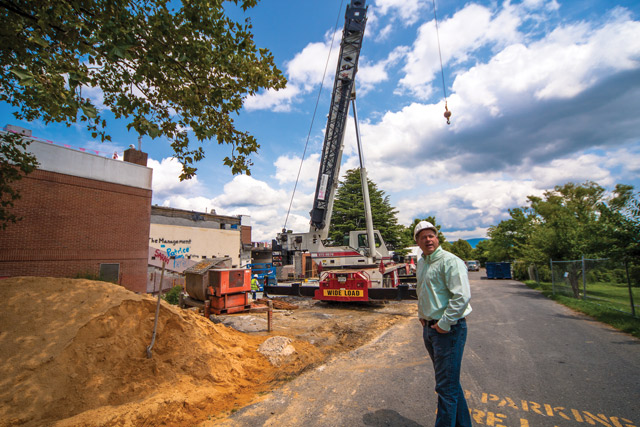 "Vice president for finance Daryl Bert '97 was caught by a photographer one July afternoon, wearing a hard hat and jeans as he personally checked out the progress of construction at the Suter Science Center. The crane is adjacent to Suter's former ""head room."" Photo by Michael Sheeler"