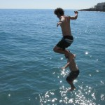 Phil and Josh jumping off of the rocks at the beach near Nerja, Spain. Photo by: Kara Lofton