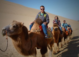 Riding camels in Dunhuang photo by Dylan Bomgardner