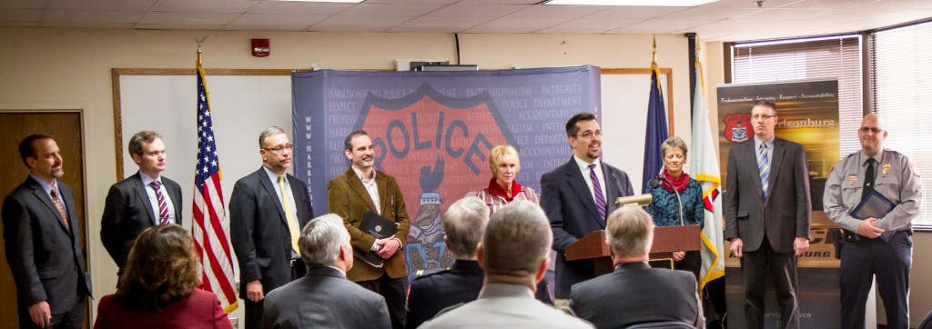 Josh Bacon, associate dean of students at JMU, talks about facilitating the first case referred to Harrisonburg Police Department's new restorative justice program.  Behind him are other members of the program's steering committee: (from left) Aaron L. Cook, attorney; chief deputy Christopher Bean, Rockingham County Commonwealth's attorney office; attorney P. Marshall Yoder; Carl Stauffer; Hillary Wing-Richards, counselor; Sue Praill and Tim Ruebke, Fairfield Center; and Lieutenant Kurt Boshart, HPD. (Photo by Jon Styer)