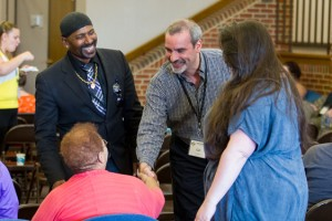 Carl Stauffer, co-director of the Zehr Institute for Restorative Justice, greets participants. To the left is Raj Sethuraju, professor in the School of Law Enforcement and Criminal Justice at Metropolitan State University.