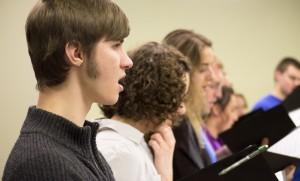 Josh Helmuth, of the Chamber Singers, practices alongside choir members. (Photo by Randi Hagi)