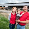 (11/2/15) - (Timberville)Andrea and Aaron Yutzy hold their 13-month-old son, Levi, in front of one of their dairy barns outfitted with solar panels. Their farm, Windcrest Holsteins, has the largest privnelry-owned solar instillation in Virginia, a $1.5 million project. (Nikki Fox/Daily News-Record)
