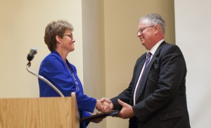 President Loren Swartzendruber accepts thanks from Kay Nussbaum, chair of the Eastern Mennonite University Board of Trustees. Swartzendruber, who retires June 30, and his wife, Pat, were celebrated at a June 24 reception and dinner at Spotswood Country Club in Harrisonburg. (Photos by Joaquin Sosa)