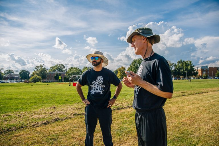 Coach Bob Hepler (left) and Associate Coach Erick Camodeca confer earlier this fall at a cross country meet.