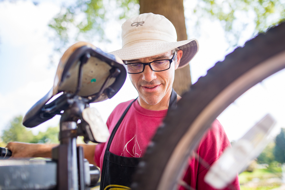Ben Wyse '99 services a bicycle at his mobile repair shop, which he regularly sets up on the campus of EMU