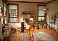 Jean Handley holds her dog in her living room, where a few pieces of art salvaged from her new Orleans home can be seen, along with newly produced items. Her Memphis house remains sparsely furnished, as she  pieces together her post-Hurricane Katrina life.