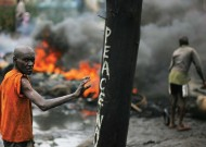 A man passes near a burning barricade in the Kibera section of Nairobi on January 18, 2008. Photo by Roberto Schmidt/AFP/Getty Images.