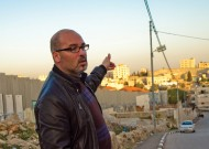 """Husam Jubran, MA '04, with Israel's """"security fence"""" at left and the Aida refugee camp at right. Photo by Jon Styer"""