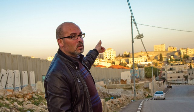 "Husam Jubran, MA '04, with Israel's ""security fence"" at left and the Aida refugee camp at right. Photo by Jon Styer"
