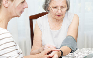 Nursing taking blood pressure of elderly woman at a kitchen table